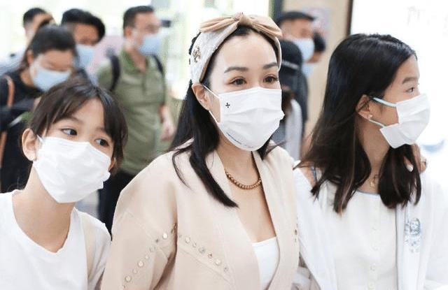 50岁钟丽缇携俩女儿现身机场,又亲又抱变少女,齐秀美腿宛如姐妹